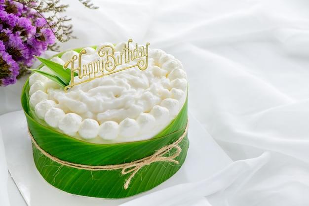Torta al burro fresca decorata con salsa di cocco e testo felice giorno di nascita su panno bianco. copia spazio e concetto di dessert