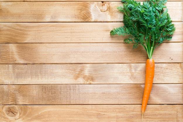 Verdura fresca della carota con i fogli sul legno.