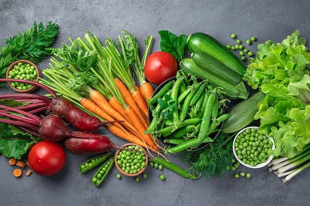 Carote fresche, barbabietole, zucchine. piselli, pomodori e verdure su sfondo blu. sfondo di verdure culinarie. vista dall'alto.