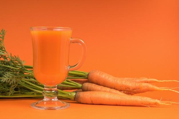 Carote fresche con erbe aromatiche e un bicchiere di frullati su uno sfondo arancione.