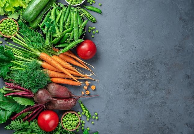 Carote fresche, zucchine, piselli, pomodori e verdure su uno sfondo blu scuro. vista dall'alto, copia dello spazio.
