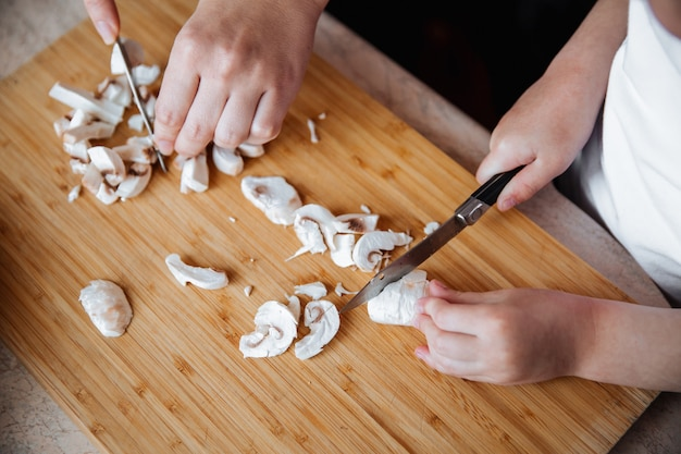 Funghi champignon freschi su una tavola di legno una ragazza e sua madre tagliano i funghi con un coltello