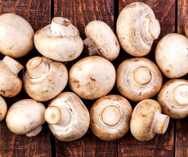 Funghi freschi del fungo prataiolo sulla tavola di legno, vista superiore. copia spazio