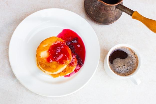 Torte di formaggio fresco con marmellata di prugne e una tazza con caffè appena preparato su una vista dall'alto del tavolo luminoso