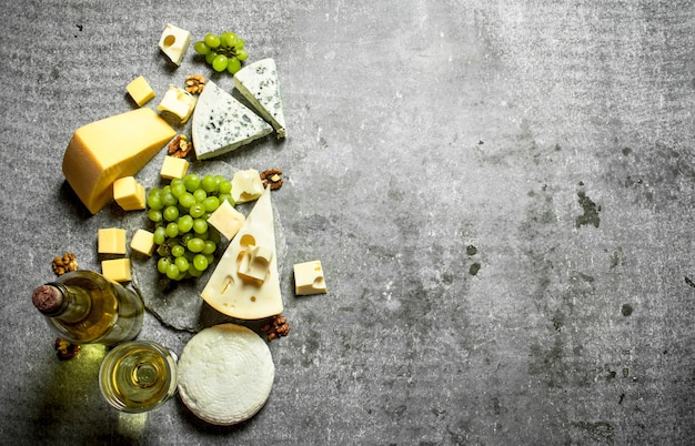 Formaggio fresco con uva e vino bianco. sul tavolo di pietra.