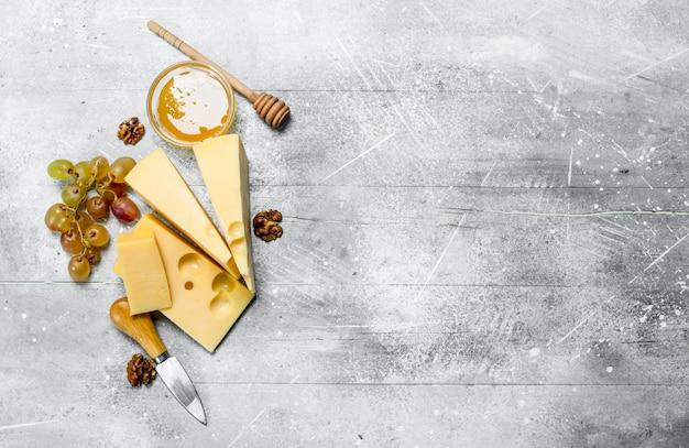 Formaggio fresco con miele e uva. su un rustico.