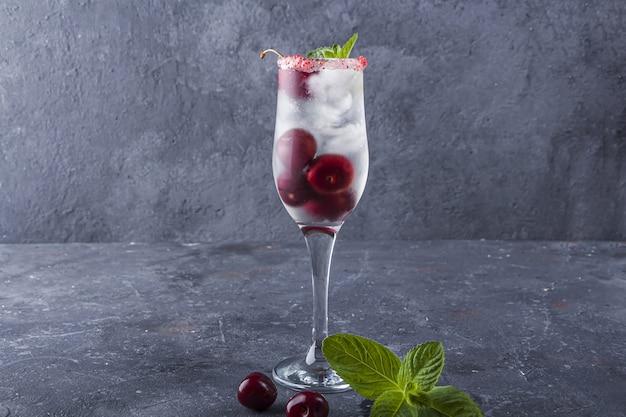 Cocktail di ciliegie fresche. martini al cioccolato e ciliegia, ciliegia ubriaca, punch. cocktail con gin o vodka, sciroppo e cubetti di ghiaccio in un bicchiere di champagne.