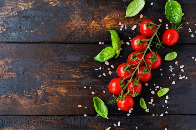 Pomodorini freschi, foglie di basilico, mozzarella e olio d'oliva su fondo di legno vecchio. ingredienti per insalata caprese. messa a fuoco selettiva.