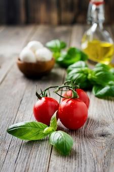 Pomodorini freschi, foglie di basilico, mozzarella e olio d'oliva su una vecchia superficie in legno. ingredienti per insalata caprese. messa a fuoco selettiva.