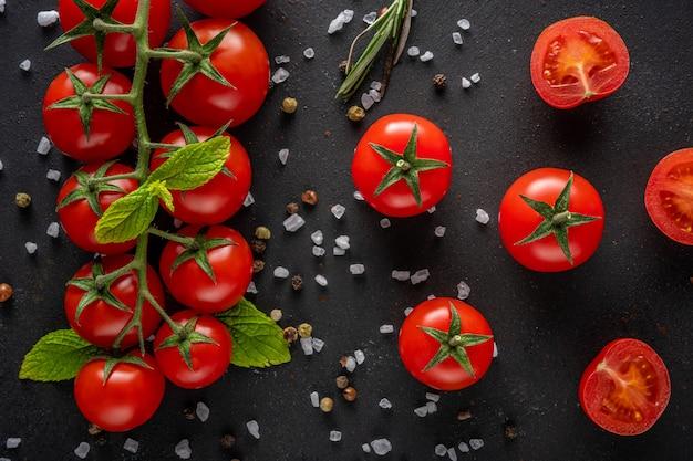 Pomodorini freschi su una scena nera con spezie