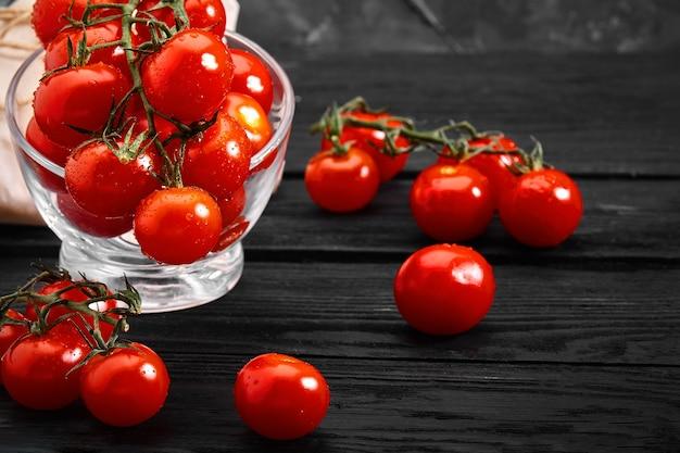 Pomodorini freschi su uno sfondo scuro, close-up. bellissimi pomodori freschi con gocce di rugiada. foto per negozi di alimentari, consegna di generi alimentari.