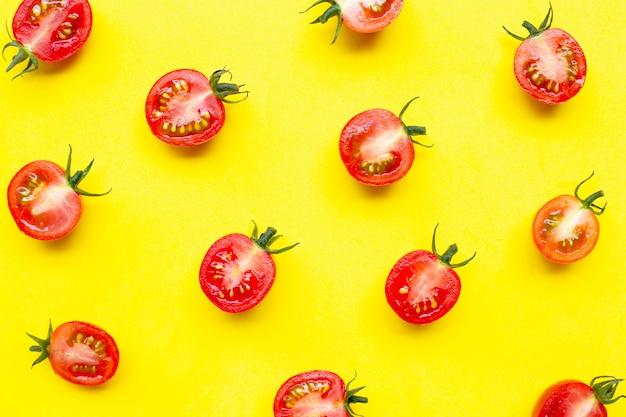 Pomodorini freschi, mezzo taglio isolato su sfondo giallo.
