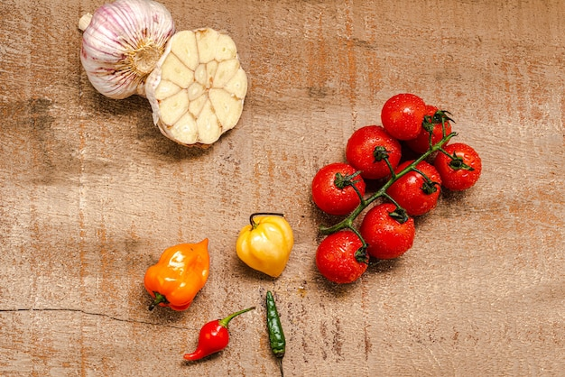 Pomodorini freschi su un fondo di legno marrone rustico con diversi peperoni e aglio a fette...