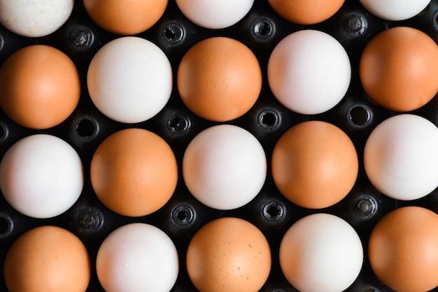Uova fresche di gallina e uova di anatra nella casella, vista dall'alto