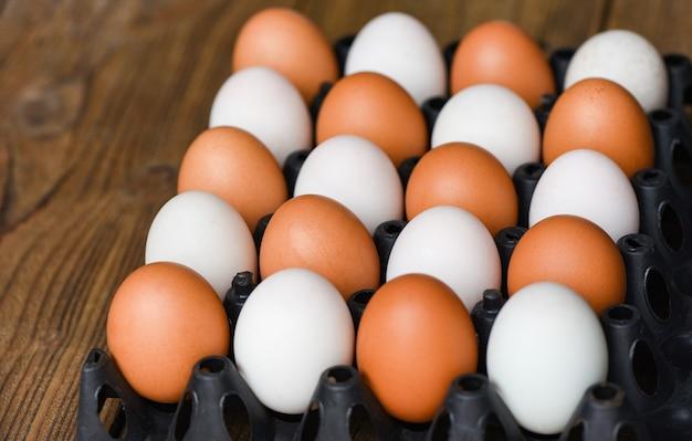 Uova di gallina fresche e uova di anatra nella casella sulla tavola di legno