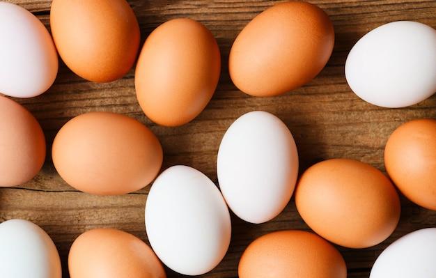 Uova di gallina fresche e uova di anatra su fondo in legno