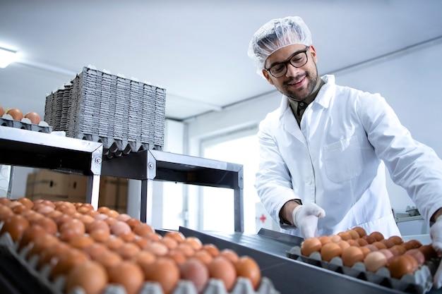 Uova di gallina fresche nella fabbrica di trasformazione alimentare che vengono spostate su nastro trasportatore e lavoratore che le prende per l'imballaggio.