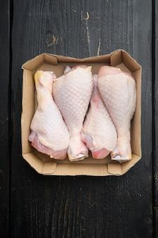 Set di cosce di pollo fresche, in confezione di carta, sul tavolo in legno nero, vista dall'alto laici piatta