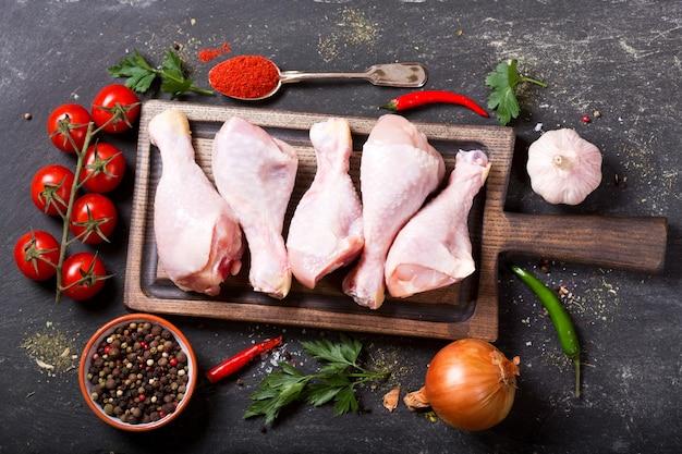 Cosce di pollo fresche sulla tavola di legno con ingredienti per cucinare, vista dall'alto