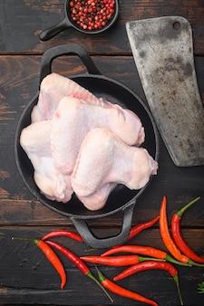 Tagli di carne di pollo fresca fattoria di carne di pollame set e vecchio coltello da macellaio mannaia, con condimento ed erbe aromatiche rosmarino e timo, sul vecchio tavolo in legno scuro, vista dall'alto piatto lay