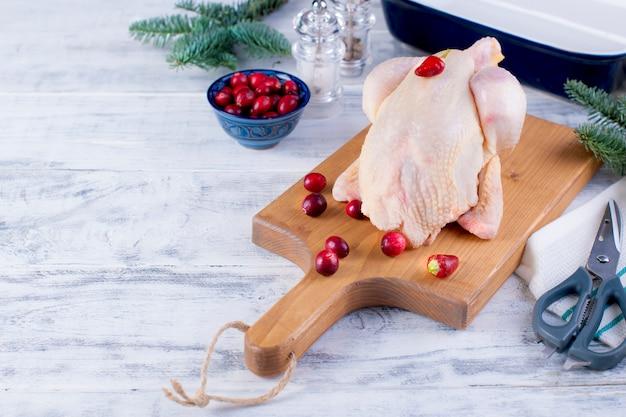 Pollo fresco su una tavola di legno con bacche rosse e rami di abete rosso