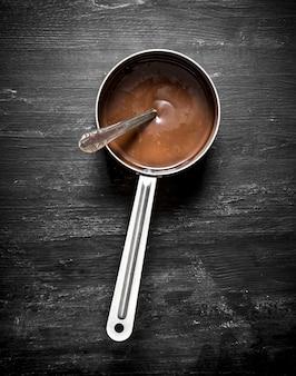 Burro al cioccolato fresco in una piccola casseruola. sul tavolo di legno nero.