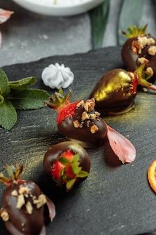 Fragole ricoperte di cioccolato fresco su sfondo grigio decorativo. concetto per la pubblicità del menu stagionale estivo.