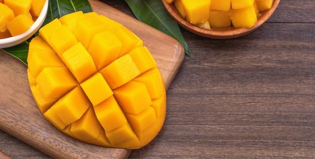 Cubetti di mango tritati freschi sul tagliere di legno