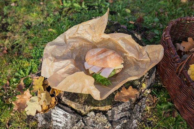 Panini freschi di baguette ciabatta con prosciutto, formaggio e lattuga su ceppo di legno rustico. stile di vita picnic autunnale all'aperto.