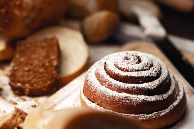 Rotolo di panino alla cannella fresco con zucchero in polvere su tavola di legno