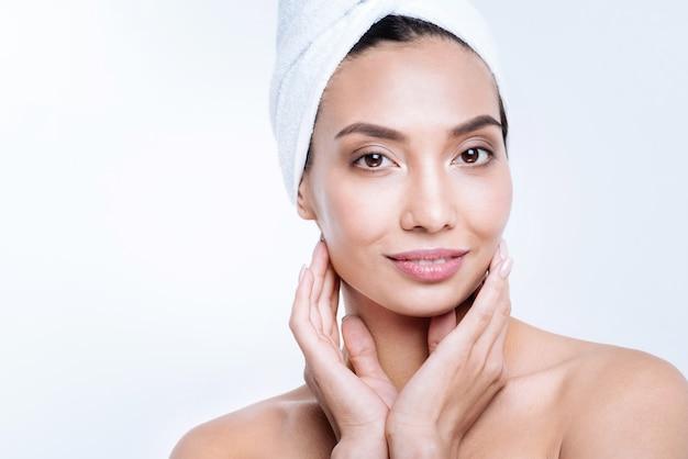 Fresco e pulito. bella donna dai capelli scuri in un turbante asciugamano toccando il viso con entrambe le mani, tenendolo a coppa, mentre posa contro un muro bianco