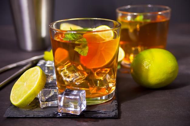 Cocktail fresco cuba libre con rum marrone, cola, menta e lime sulla superficie nera. long island iced tea cocktail.