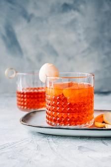 Cocktail fresco in vetro con succo d'arancia su sfondo blu. negroni con buccia d'arancia su un piatto.