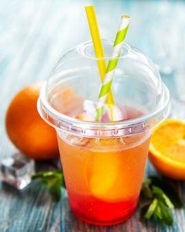 Cocktail fresco con arancia e ghiaccio. bevanda alcolica e analcolica su fondo di legno blu