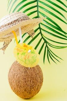 Cocktail fresco della noce di cocco con cannucce e foglia di palma