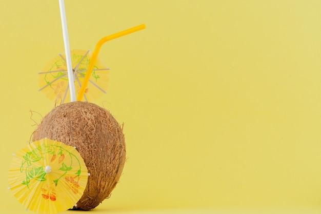 Cocco fresco cocktail con cannucce su sfondo giallo, copia dello spazio.