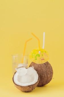 Cocktail di cocco fresco con cannucce su sfondo giallo