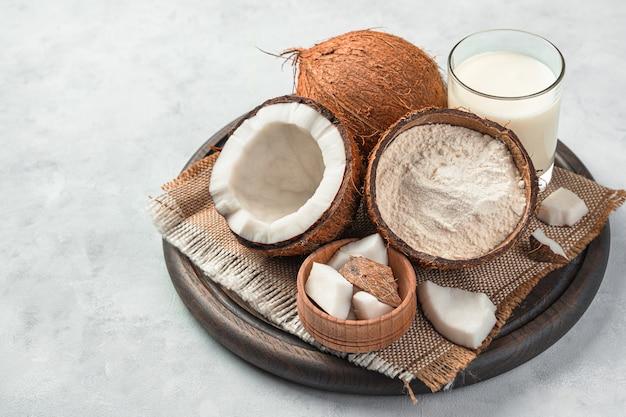 Cocco fresco e prodotti a base di cocco su sfondo grigio. farina di cocco e latte di cocco.