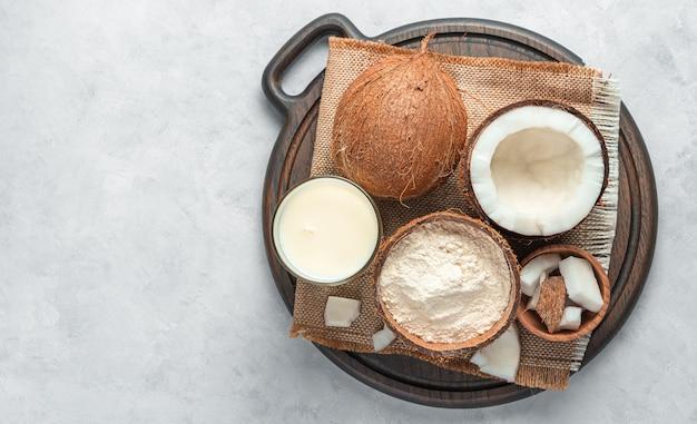 Cocco fresco e prodotti a base di cocco: latte e farina su sfondo grigio. vista dall'alto, copia dello spazio.