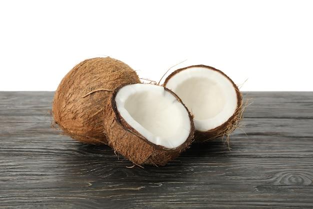 Noce di cocco fresca sulla tavola di legno, isolata su bianco