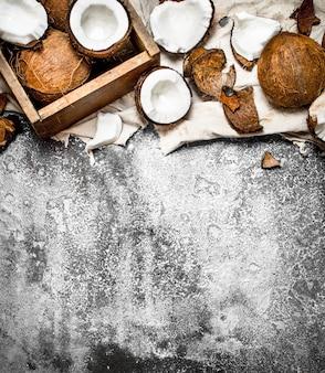 Noci di cocco fresche in una vecchia scatola sul tessuto