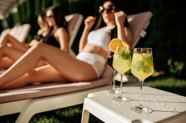 Cocktail freschi, svaghi femminili sui lettini. belle ragazze si rilassano a bordo piscina in una giornata di sole, vacanze estive di amiche attraenti