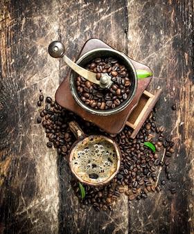 Caffè fresco in una tazza di argilla con un vecchio macinino da caffè. su uno sfondo di legno.