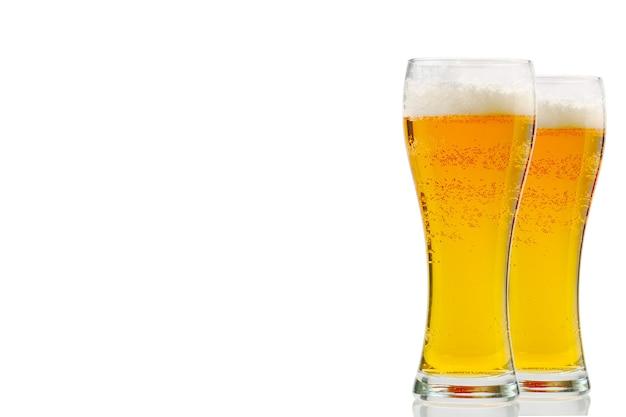 Bicchiere di birra fredda fresca isolato su baviera di birra in oro bianco con pinta di corona di schiuma di birra chiara su superficie bianca