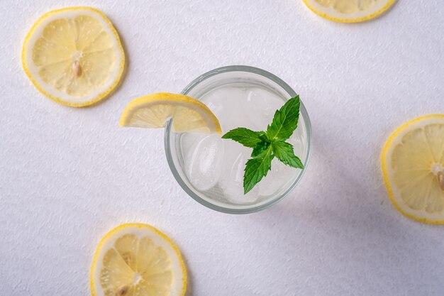 Bere acqua fresca fredda chiara in vetro con cubetti di ghiaccio, fetta di limone e foglia di menta, vista dall'alto