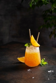 Cocktial freddo fresco con arancia, ghiaccio tritato e menta e concetto di bar