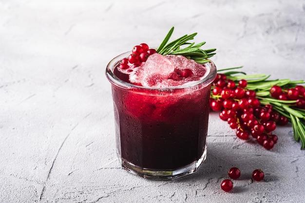 Cocktail di frutta fresca fredda in vetro, rinfrescante bevanda estiva a bacca di ribes rosso con foglie di rosmarino