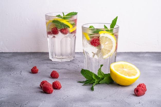 Bevanda fresca di acqua ghiacciata fredda con limone, lamponi e foglia di menta in due bicchieri sfaccettati