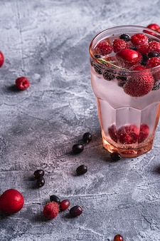 Bevanda fresca e fredda di acqua frizzante con ciliegia, lampone e bacche di ribes in vetro sfaccettato rosso sul tavolo in cemento, bevanda dietetica estiva, vista angolare