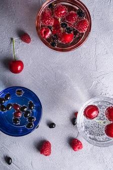Bere acqua frizzante fredda fresca con bacche di ciliegia, lampone e ribes in tre vetri colorati su pietra